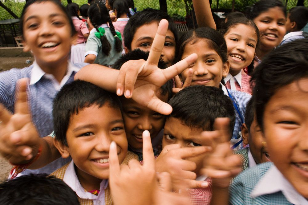 a group of school children smiling and gesturing towards the camera