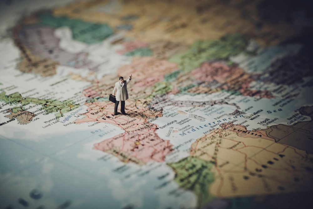 a toy figurine of a man hailing a taxi stood on a map of europe