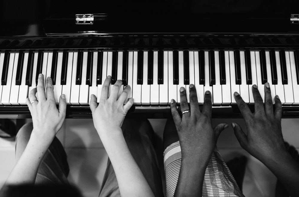 piano teacher demonstrating technique to a student
