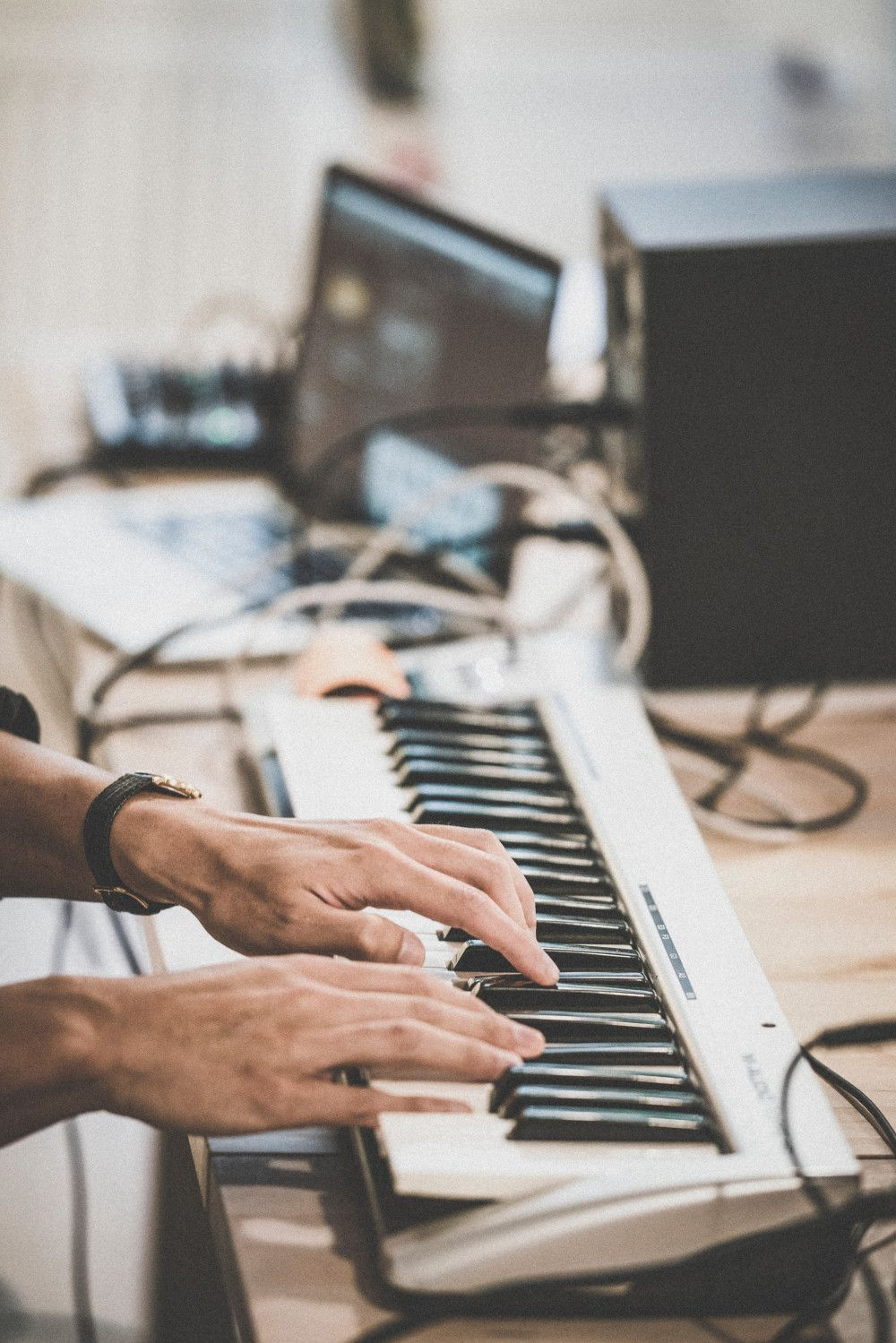 a man playing a keyboard with a computer in the background