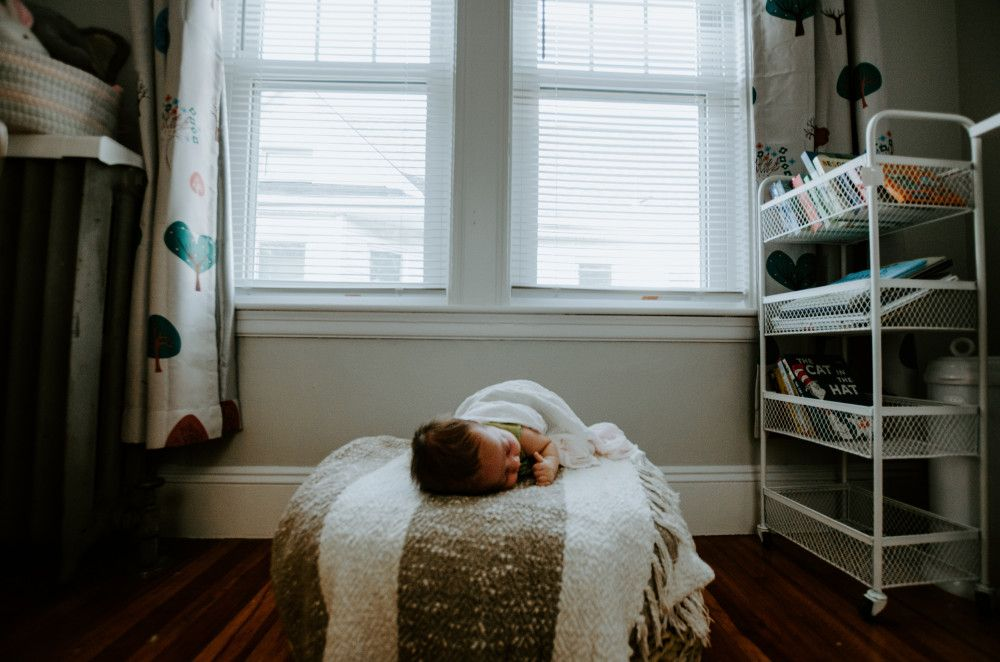 child asleep on a cushion underneath a window
