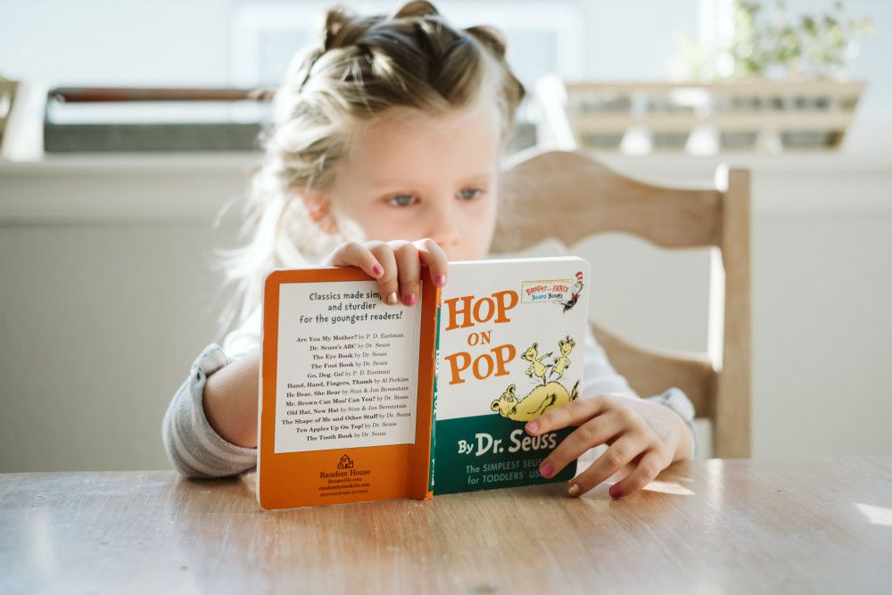 child sitting at the kitchen table reading hop on pop by dr seuss