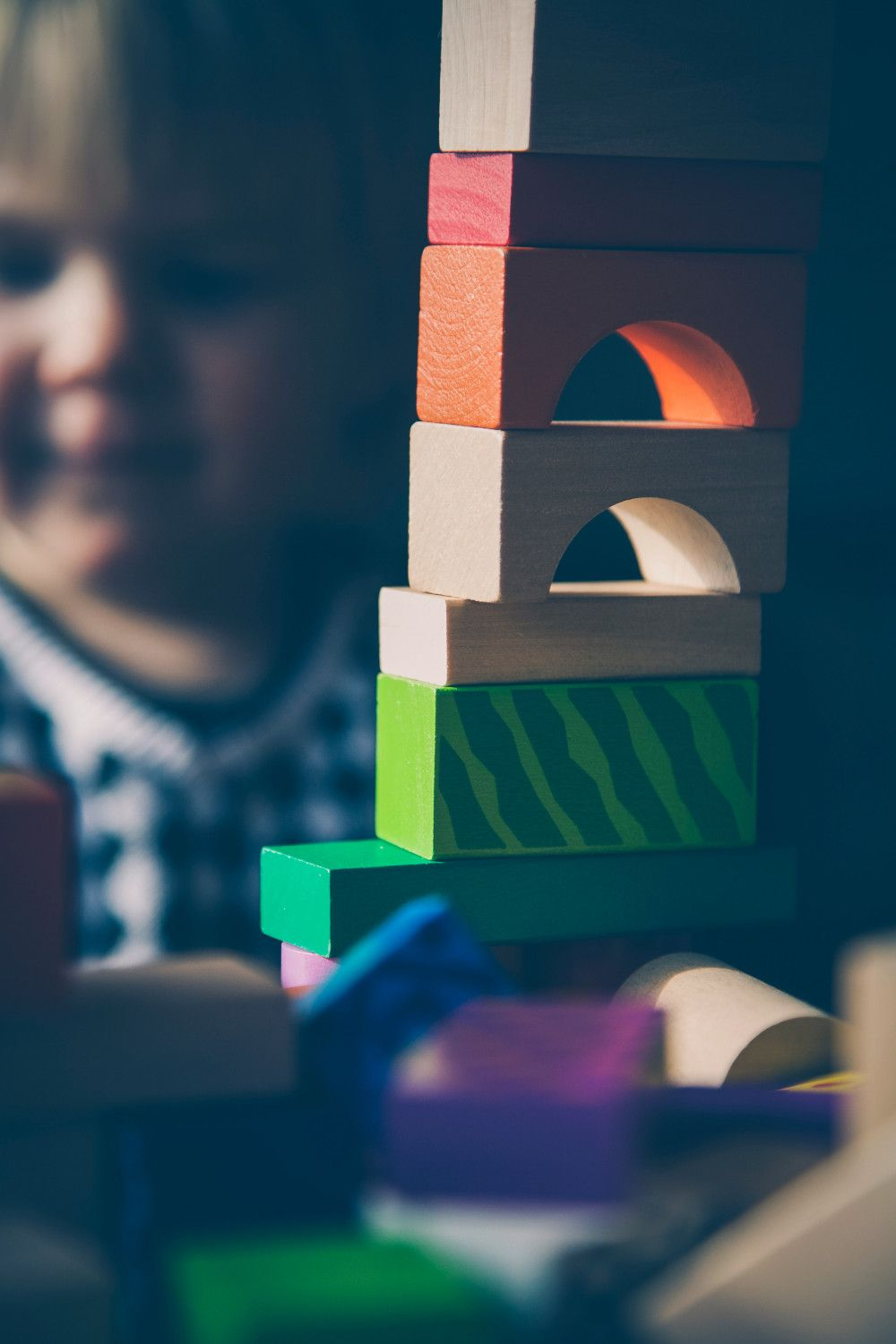 a child stood behind a tower made out of wooden play blocks