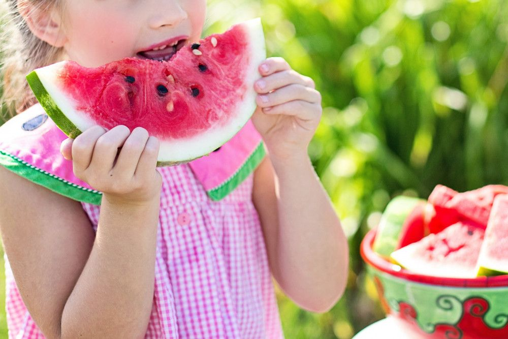 child taking a bite out of a slice of watermelon