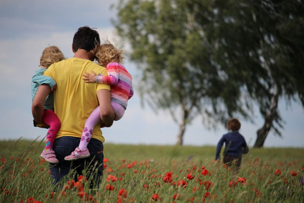 Dad holding children in each arm walking through a field