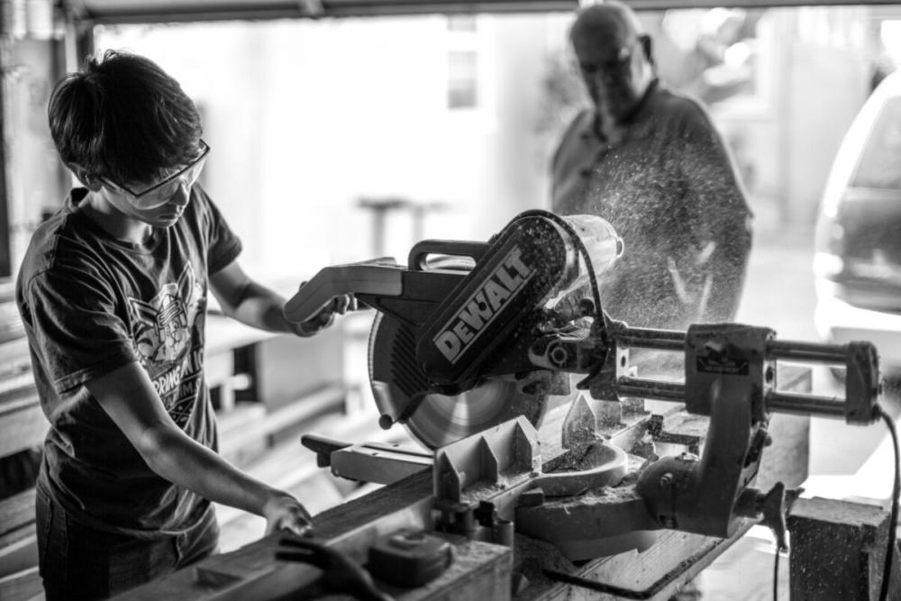 boy using saw on apprenticeship