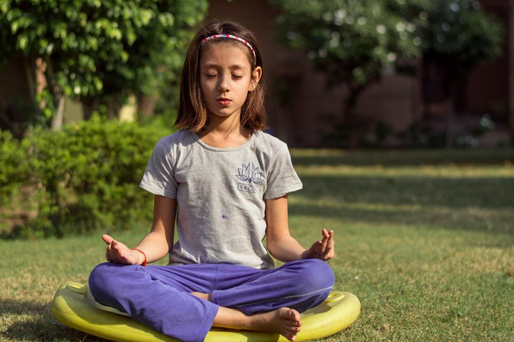 girl doing meditation in garden