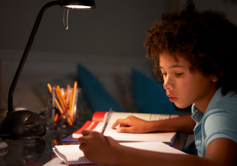 young-boy-studying-at-desk-in-bedroom-in-evening